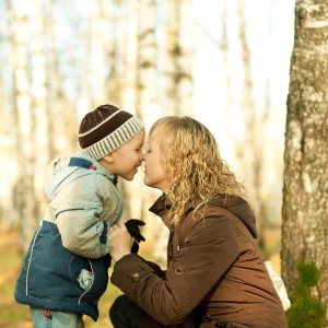 Mother and son having fun in an autumn forest.